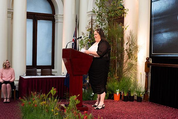Dee-Jay stands at a podium making a speech